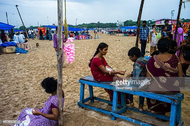 A woman left makes flower garlands while another woman and a boy share some fish at a food stall on Marina Beach in Chennai Tamil Nadu India on...