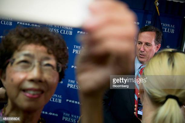 A woman left takes a selfie photograph with Rick Santorum former senator from Pennsylvania and 2016 Republican presidential candidate after a news...