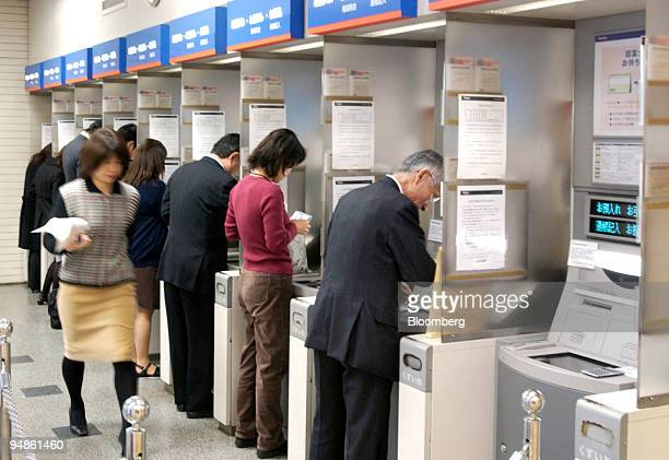 A woman left walks toward an open ATM at a Mizuho Bank branch in downtown Tokyo on Monday December 20 2004 Mizuho Financial Group Inc Japan's biggest...