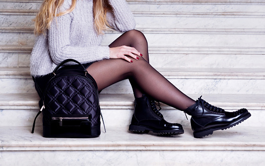 Woman legs in black ankle boots with bag. 947152114