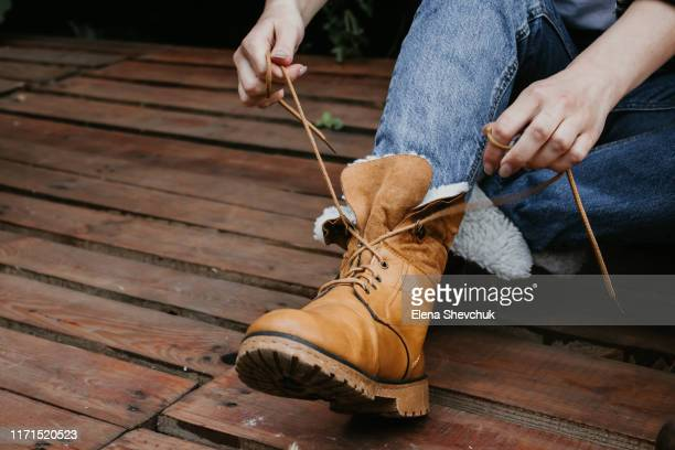 woman legs in blue jeans and brown boots on wooden floor - ブーツ ストックフォトと画像