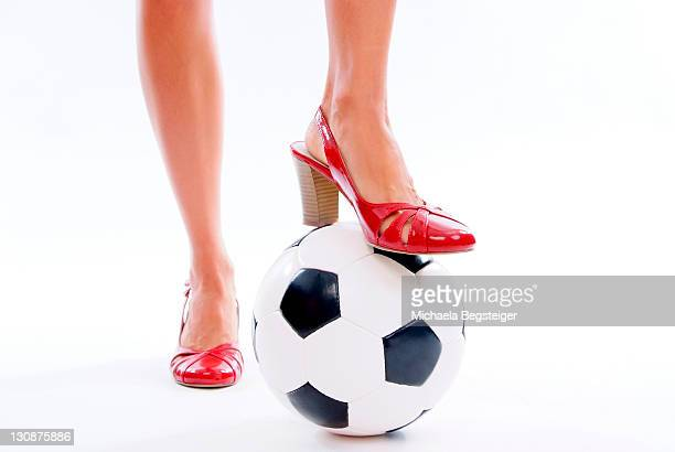 woman legs in high heeled shoes with soccer ball