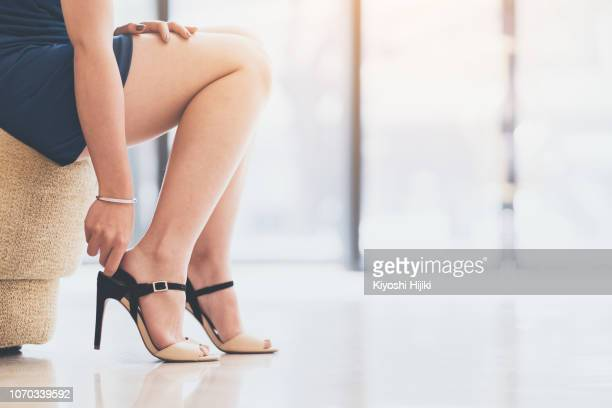 woman legs in short skirt wearing high heel - legs and short skirt sitting down stock photos and pictures