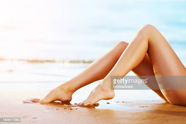 woman legs on the sunset beach - leg stock pictures, royalty-free photos & images