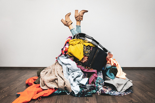 woman legs out of a pile of clothes on the floor. shopping addiction concept 1190179908