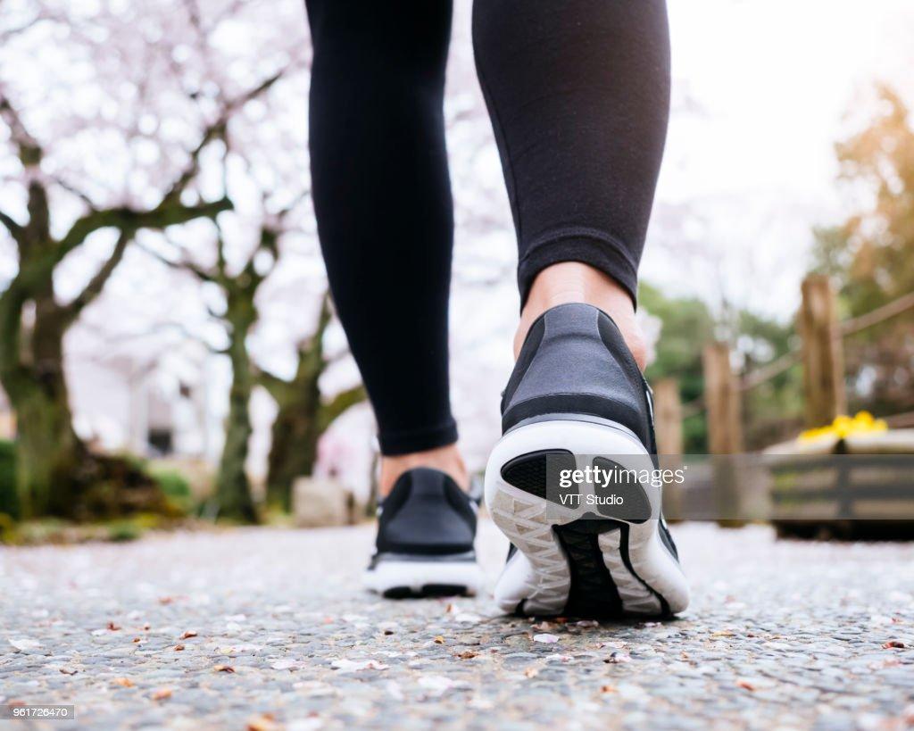 Woman Legs Sport shoe walk in Park outdoor Sakura tree : Stock Photo