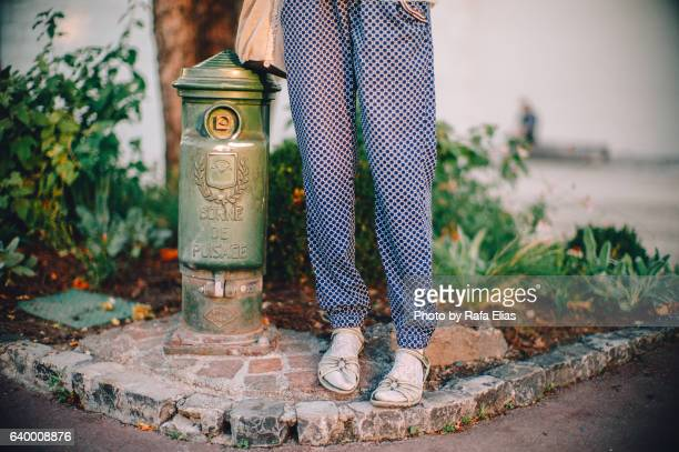 woman legs standing next to hydrant - baggy pants stock photos and pictures