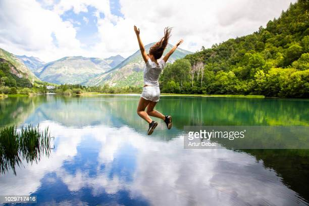 woman levitating over stunning landscape with water reflection on lake. - reportaje imágenes stock pictures, royalty-free photos & images