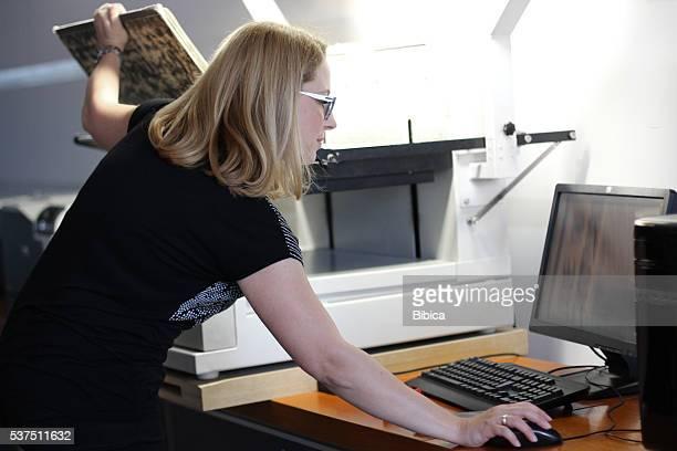 Femme Bibliothécaire de numérisation de grandes feuilles de journal