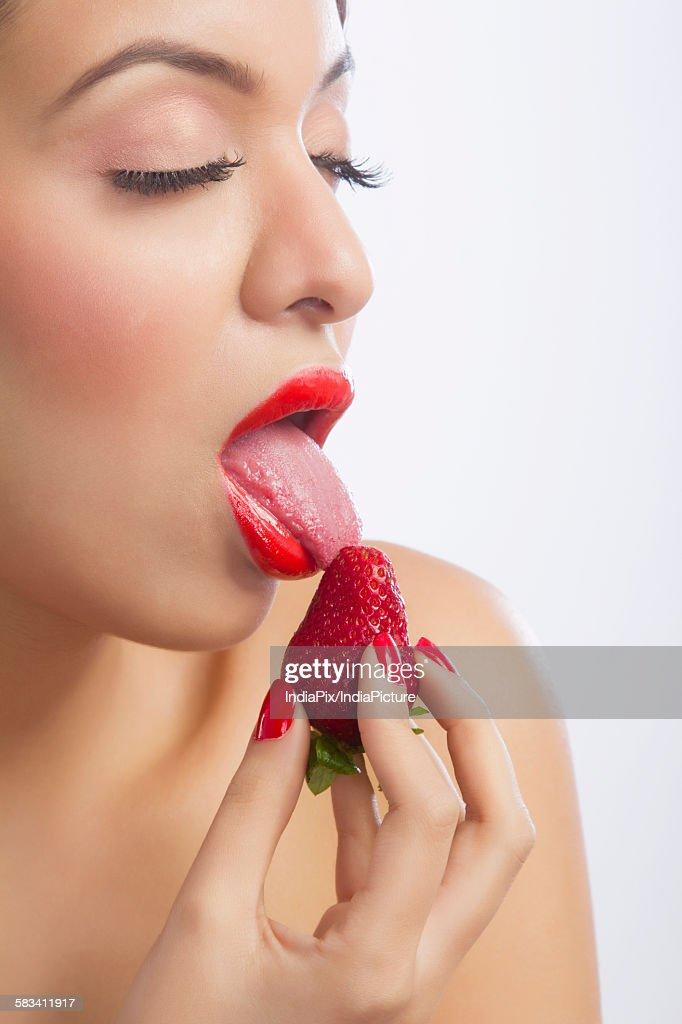 Woman licking a strawberry : Stock Photo