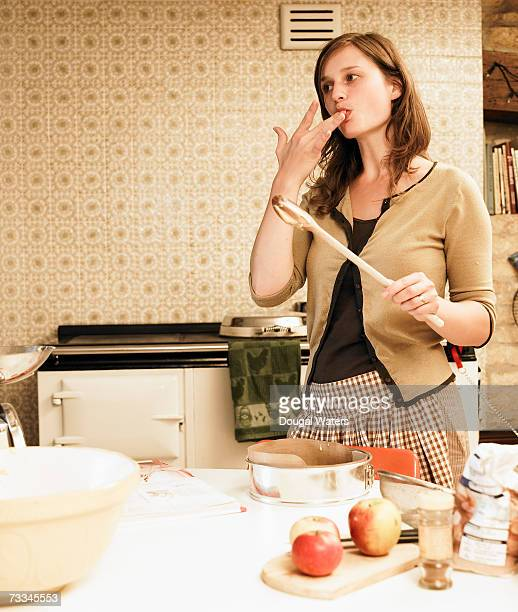 Woman licking fingers baking in kitchen