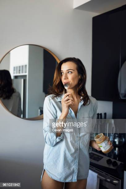 Woman licking spoon while standing in kitchen