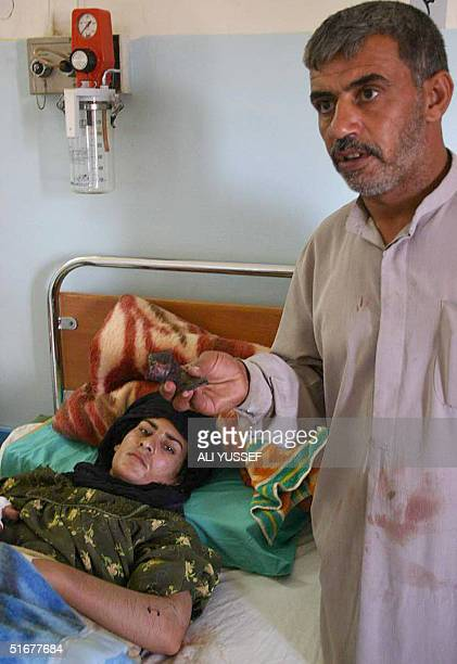 A woman lies in a hospital bed as a relative shows off a piece of shrapnel in Baquba 60 kms northeast of Baghdad 05 November 2004 Two children were...