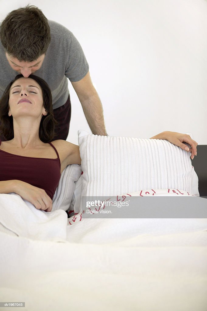 Woman Lies in Bed, Her Husband Behind Her, Kissing Her Forehead : Stock Photo