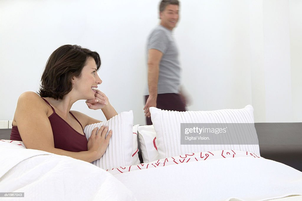 Woman Lies in Bed, Looking Back and Smiling at Her Husband in the Background : Stock Photo