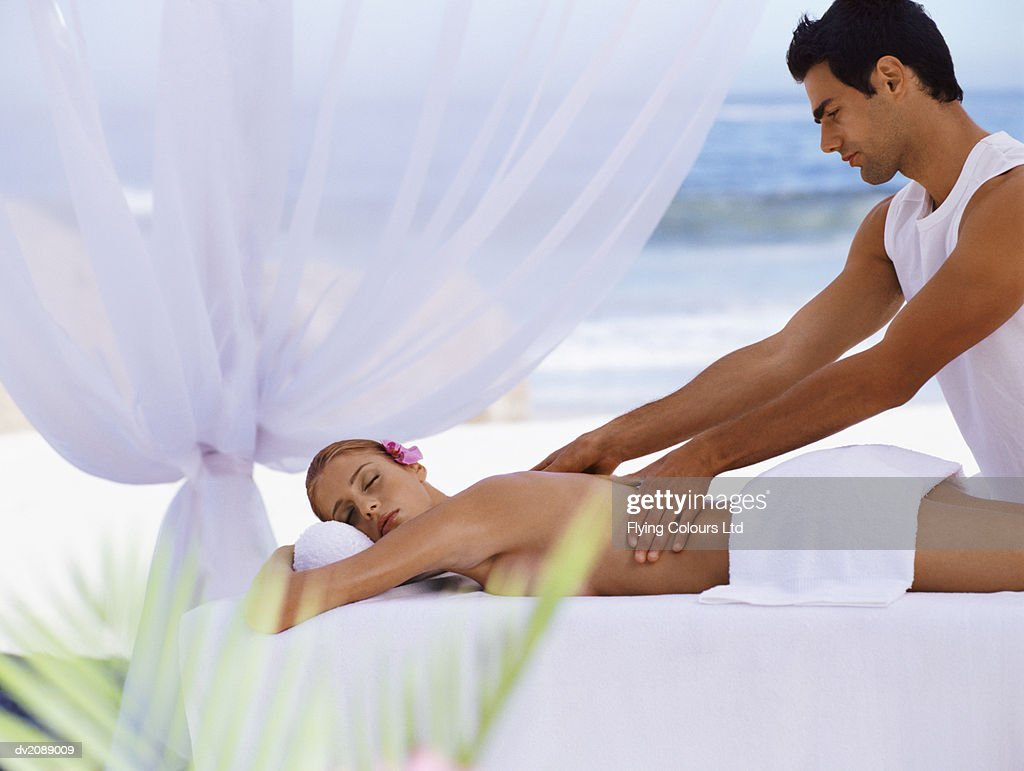Woman Lies on a Balcony Having Her Back Massaged by a Man : Stock Photo