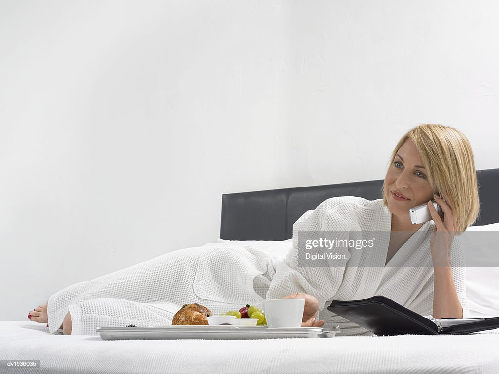 Woman Lies on a Bed in a Hotel Room With a Breakfast Tray and Using a Mobile Phone : Stock Photo