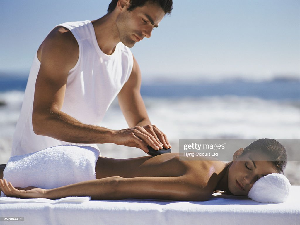 Woman Lies on a Bed Outdoors, Having Her Back Massaged With a Stone by a Male Therapist : Stock Photo
