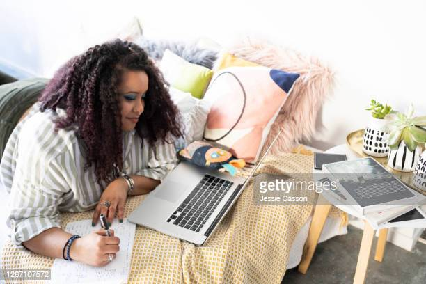 a woman lies on a bed working on her laptop - bed stock pictures, royalty-free photos & images
