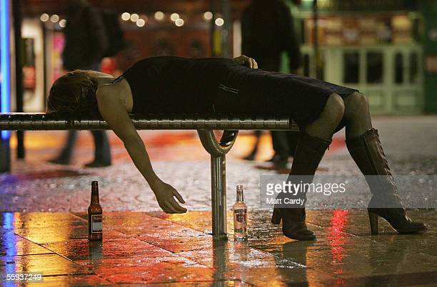 Woman lies on a bench after leaving a bar in Bristol City Centre on October 15, 2005 in Bristol, England. Pubs and clubs are preparing for the new...