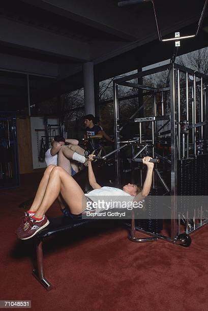 A woman lies on a bench and performs a bench press as a man next to her does an inclined situp on a multi station weight machine in a gymnasium early...