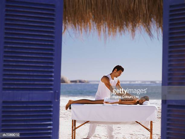 Woman Lies on a Bench on the Beach, Having Her Back Massaged by a Male Masseur