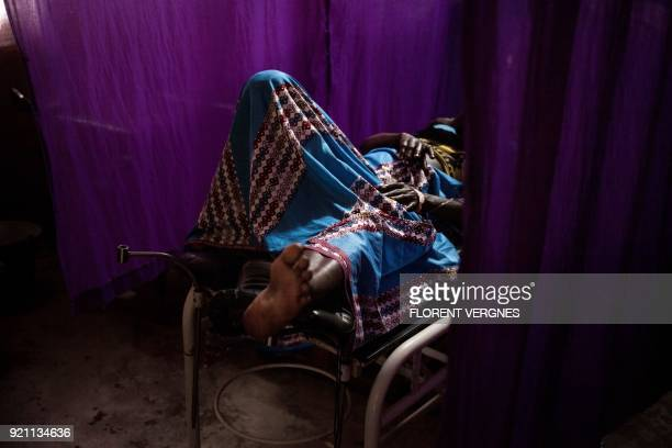 A woman lies on a hospital bed after having a miscarriage at Boali maternity ward which has only one doctor and no running water on February 14 2018...