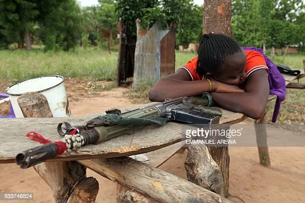 A woman lies on a riffle which she claims belong to her husband for selfdefence after attacks by Fulani herdsmen at OkokoloAgatu in Benue State...