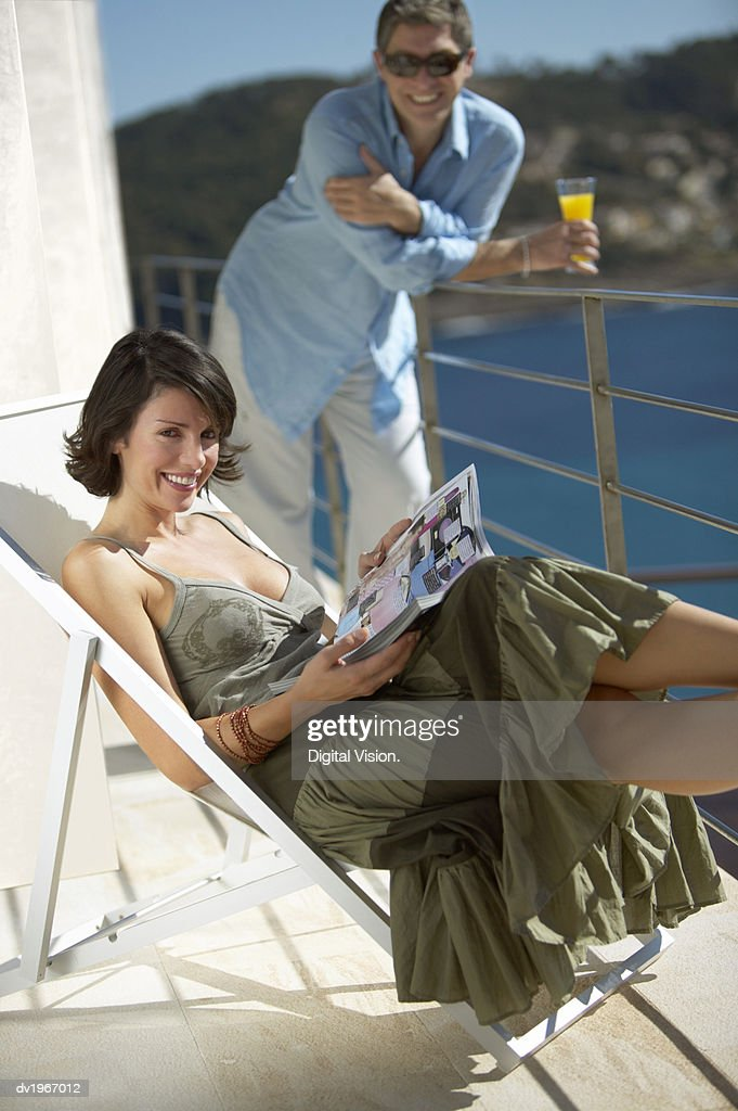 Woman Lies on a Sun Lounger on a Balcony With Her Husband, a Magazine in Her Lap : Stock Photo