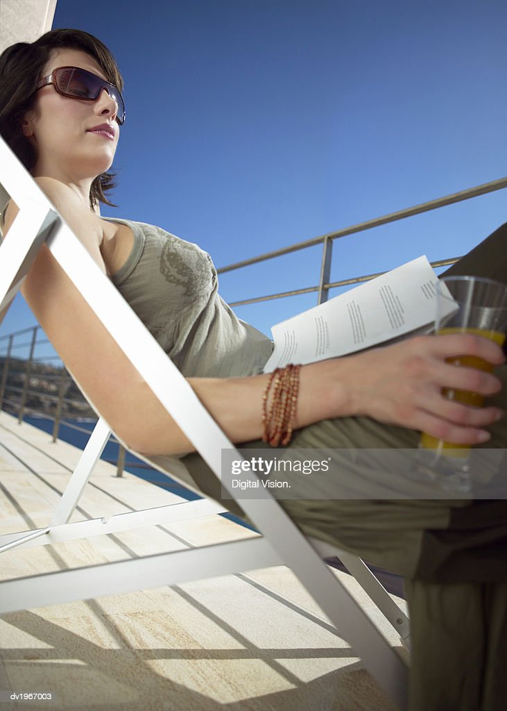 Woman Lies on a Sun Lounger on Her Balcony With a Book in Her Lap : Stock Photo