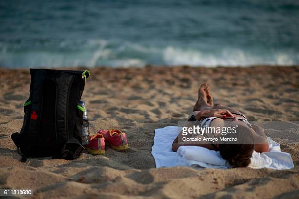A woman lies on the beach close to an Ironman Barcelona bag the day before of the Ironman Barcelona on October 1 2016 in Calella Spain