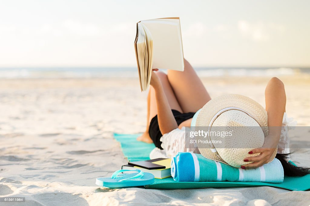 Woman lies on the beach reading a book : Stockfoto