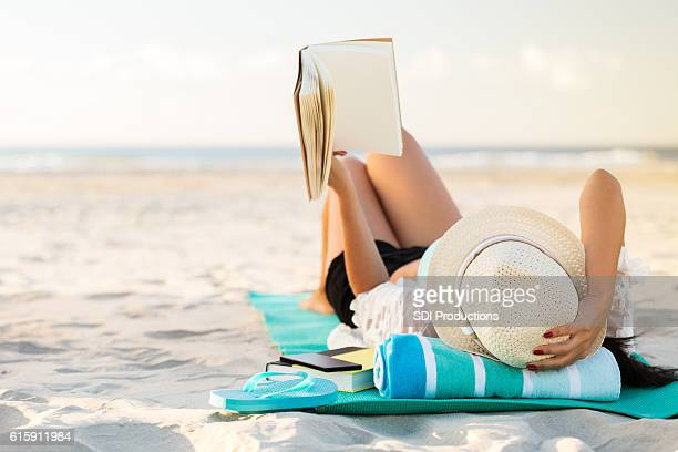 woman lies on the beach reading a book - badkleding stockfoto's en -beelden