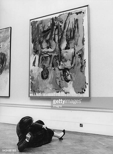 A woman lies on the floor while she looks at the painting Family by Georg Baselitz The images are hanged upside down so that the exhibition visitors...