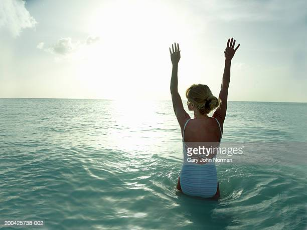 Woman lifting arms in ocean, rear view