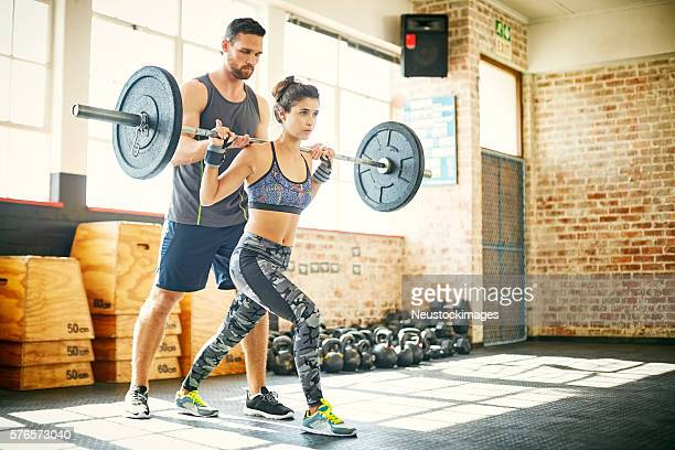 Woman lifting barbell while personal trainer assisting her in gy