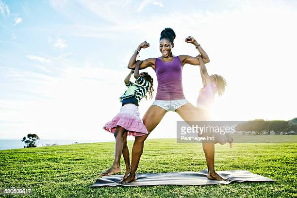 woman lifting children with biceps in park - strength stock pictures, royalty-free photos & images