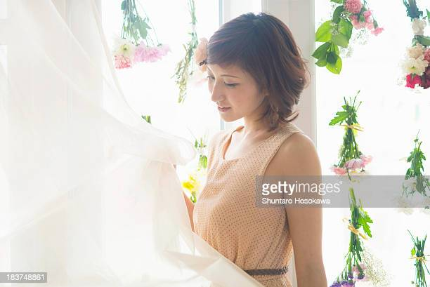 Woman lifting curtains of glass windows with dangling flowers