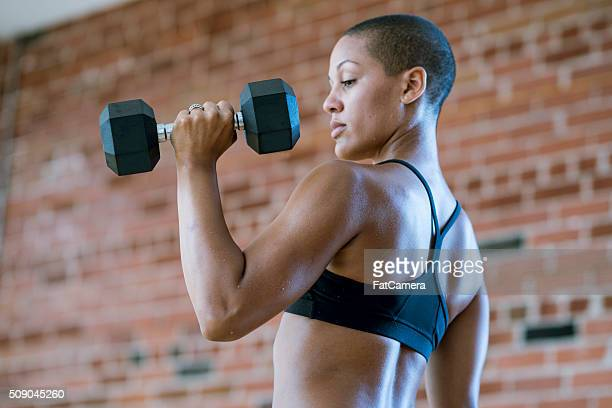 woman lifting dumbbells - black female bodybuilder stock photos and pictures
