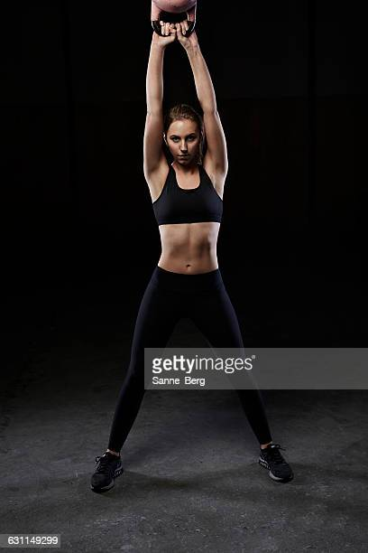 Woman lifting kettle bell above her head in a gym