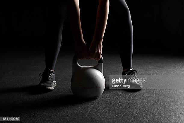 Woman lifting kettle bell in a gym