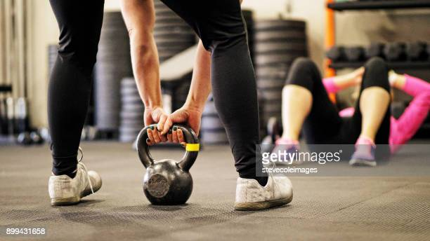 Woman lifting kettlebell in gym.