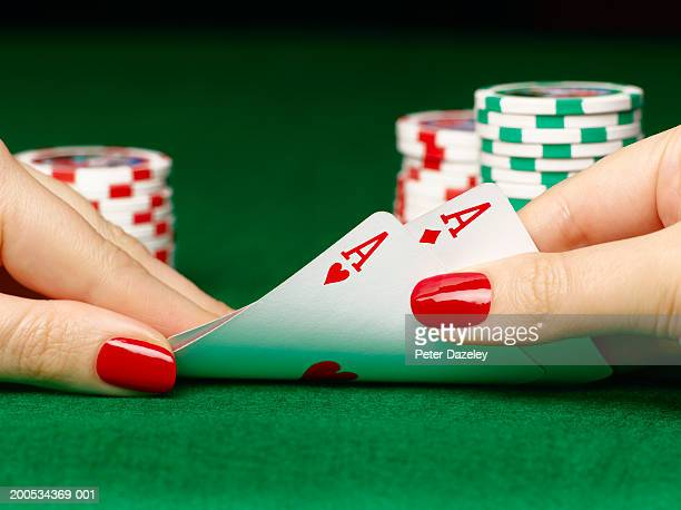 Woman lifting playing cards off table, close-up of hands