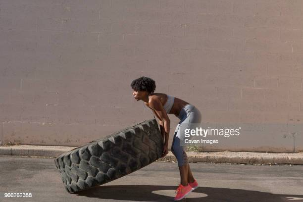 woman lifting tire truck while exercising against wall - circuit training stock photos and pictures