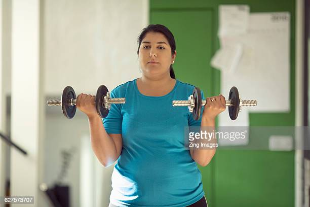 woman lifting weights at home - arab women fat stock pictures, royalty-free photos & images