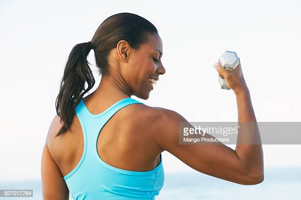 woman lifting weights on beach - ponytail stock pictures, royalty-free photos & images