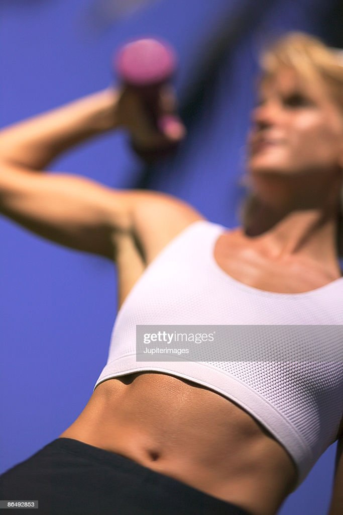 Woman lifting weights : Stock Photo