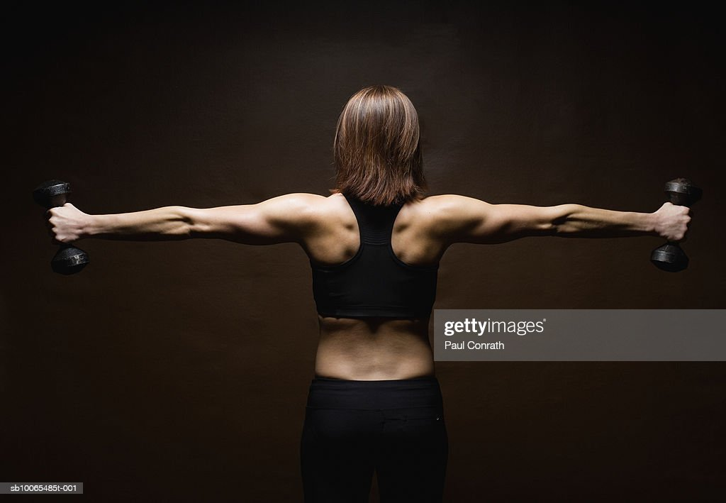 Woman lifting weights, rear view : Stock Photo