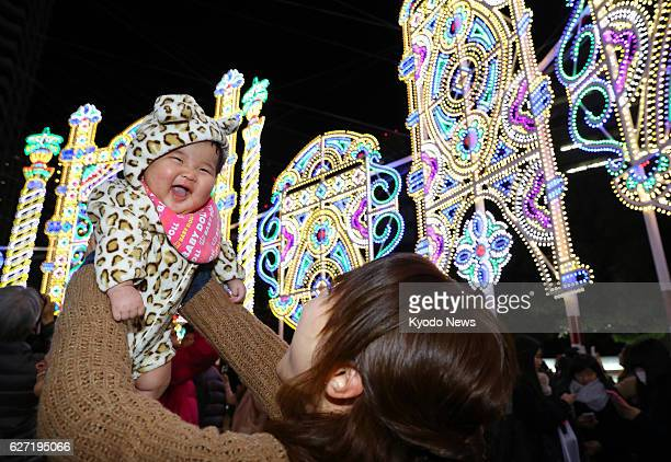 A woman lifts a baby at the Kobe Luminarie light festival held to commemorate victims of the 1995 Great Hanshin Earthquake in the western Japan port...