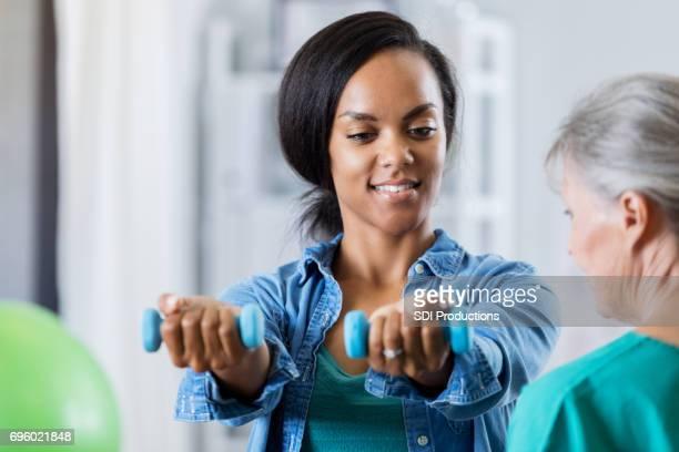 Frau hebt Hand Gewichte in physikalische Therapie-Sitzung